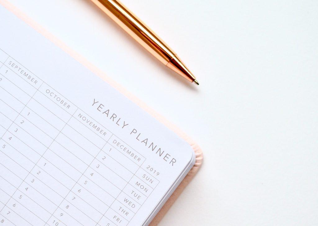 Agenda et stylo bille sur un bureau blanc