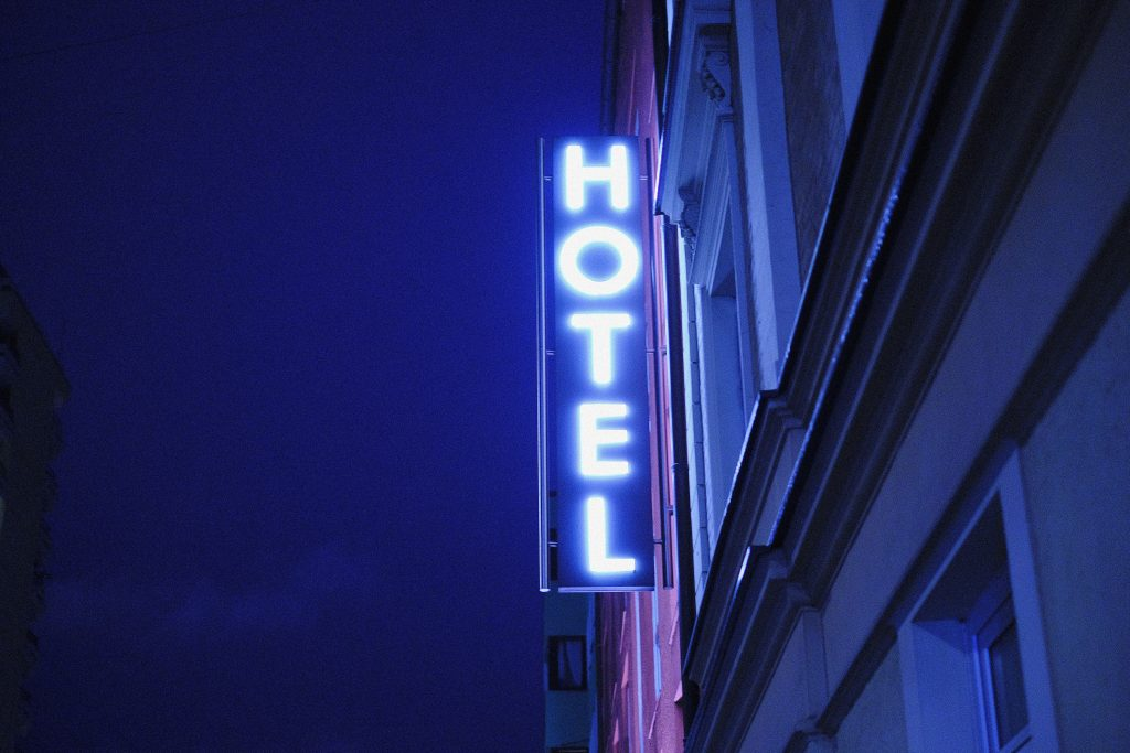 """Néon bleu """"Hotel"""" sur la façade d'un immeuble"""