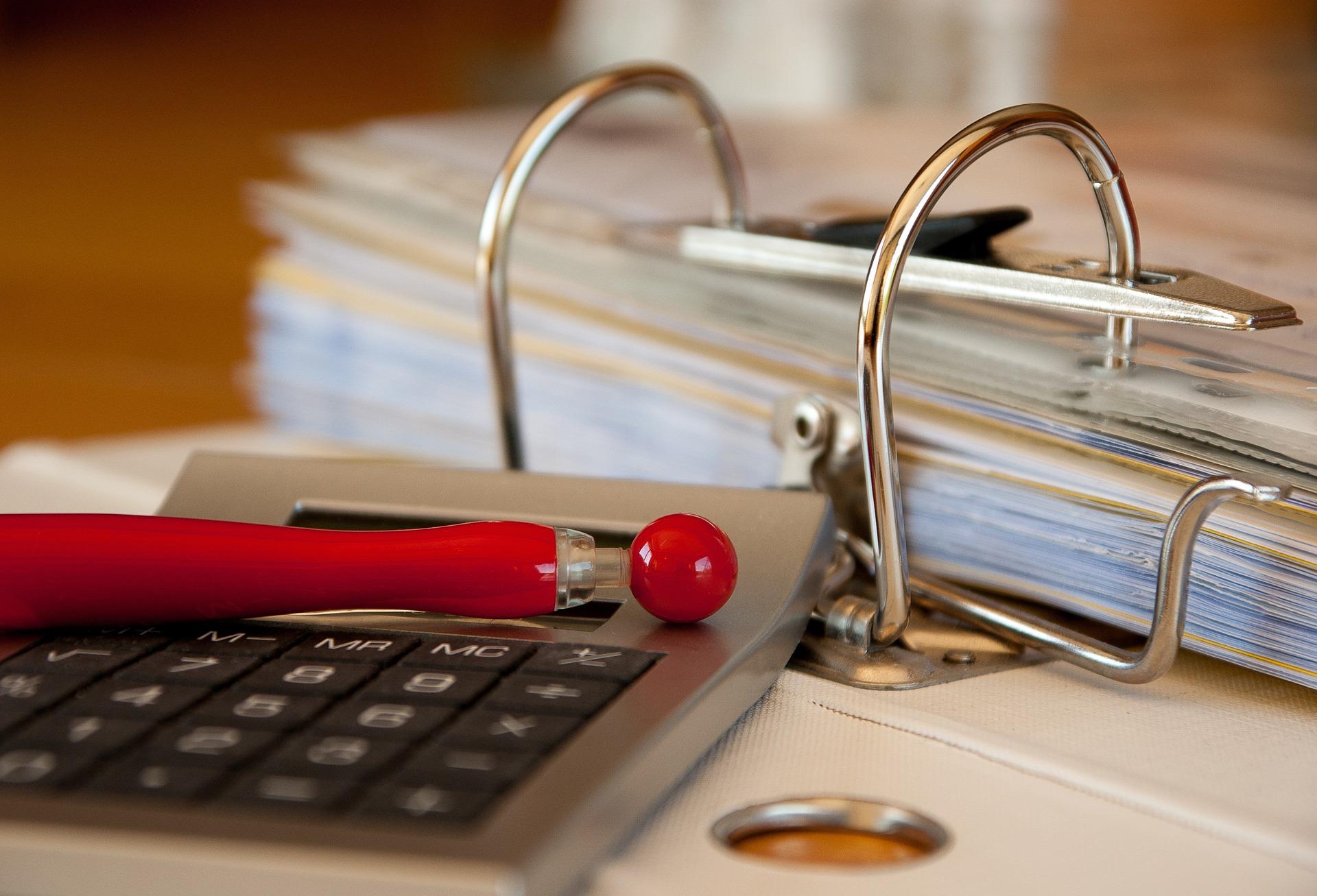 classeur calculette et stylo rouge pour comptabilité