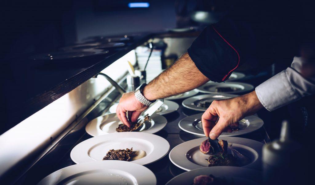 Cuisinier qui dresse des assiettes en cuisine