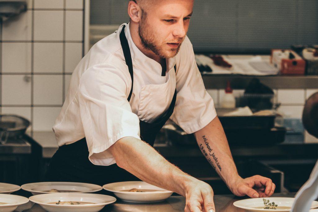 Cuisinier qui prépare des assiettes en cuisine