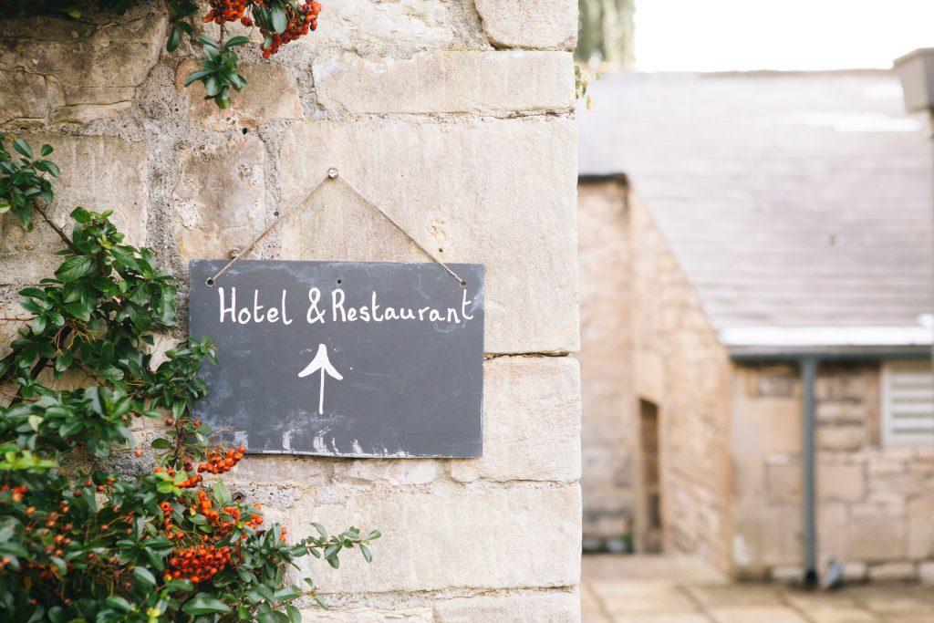 """Petite ardoise """"Hôtel & Restaurant"""" accrochée sur un mur en pierre dans un village"""