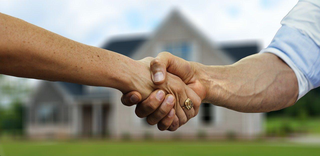 deux personnes qui se serrent la main devant une maison en arrière plan
